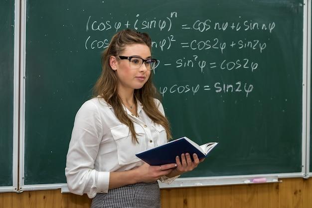 Insegnante con libro in classe. le formule matematiche scrivono sulla lavagna.