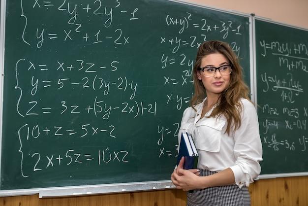 Insegnante con libro che guarda l'obbiettivo in aula. le formule matematiche scrivono nella lavagna. di nuovo a scuola