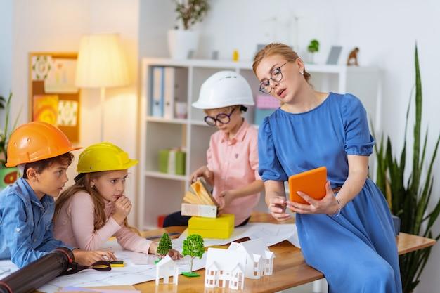 Insegnante con tablet. insegnante con gli occhiali con una tavoletta arancione che racconta agli alunni la modellazione della casa
