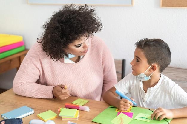 Insegnante che lavora con un bambino in età prescolare durante l'epidemia di coronavirus - soft focus sull'occhio della donna