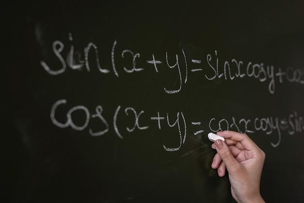 Insegnante scritto sulle formule matematiche del consiglio scolastico. algebra