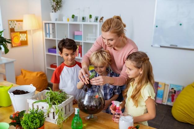 Insegnare agli alunni. utile giovane insegnante di botanica intelligente che insegna ai suoi alunni a prendersi cura delle piante