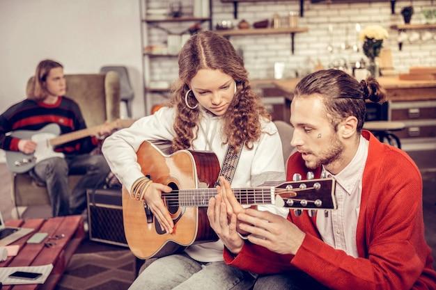 Insegnare agli adolescenti. insegnante di musica barbuto che insegna agli adolescenti a suonare la chitarra in soggiorno