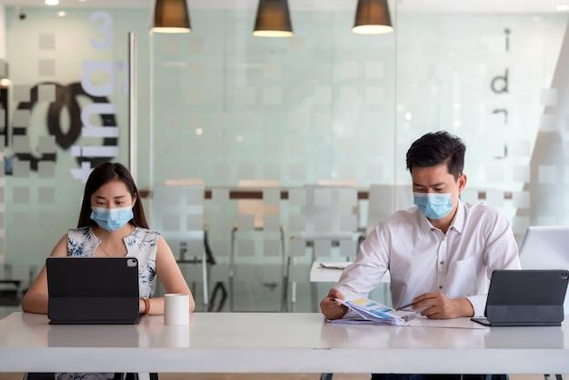 Il team di uomini d'affari asiatici che lavorano insieme indossano maschere distanti per prevenire i germi in ufficio.