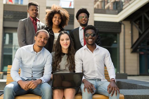 Squadra di belle persone africane sulla panchina con il portatile in estate