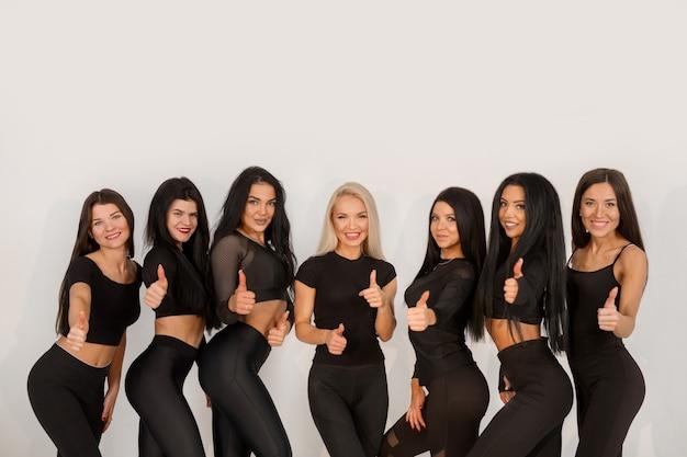 Squadra di belle giovani donne in tute nere su sfondo bianco