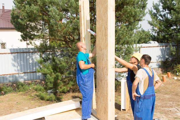 Team di costruttori che montano pannelli prefabbricati in legno sul cantiere di una nuova casa in costruzione