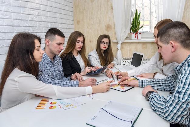 Team di analisti aziendali che lavorano con grafici aziendali