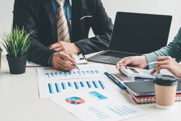 Analisi di brainstorming di uomini d'affari di squadra utilizzando la calcolatrice che rappresenta graficamente il successo in ufficio.