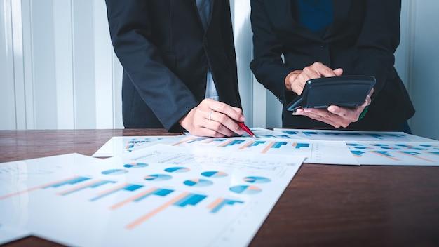Donna d'affari di squadra che analizza i dati finanziari e calcola il grafico dei grafici.