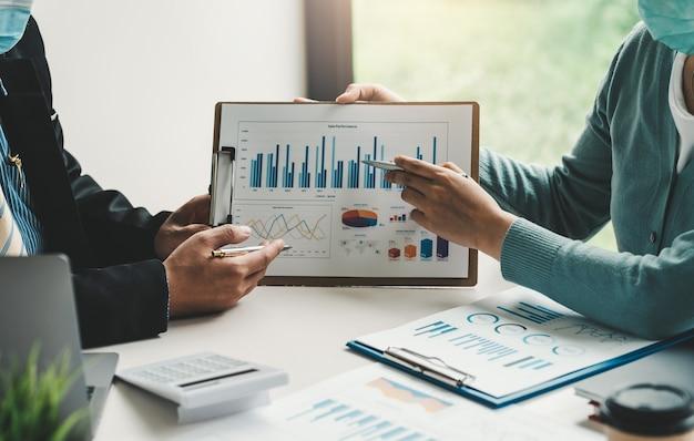 Team di uomini d'affari con penna che punta a un grafico che presenta il loro lavoro in ufficio. Foto Premium