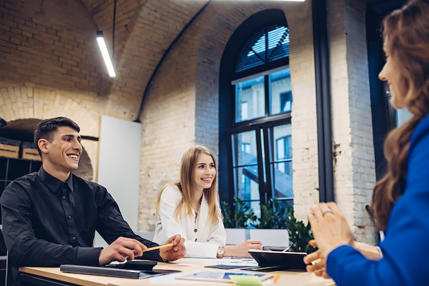 Team di imprenditori che discutono insieme al tavolo in ufficio