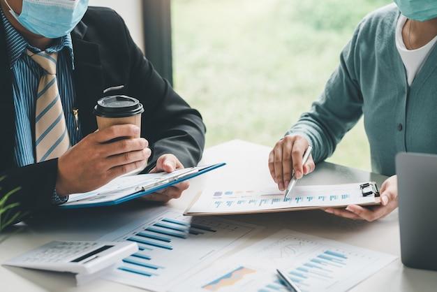 Un team di uomini d'affari sta analizzando un grafico del reddito statistico utilizzando una calcolatrice e indicando il grafico indossa una maschera per prevenire i germi in ufficio.