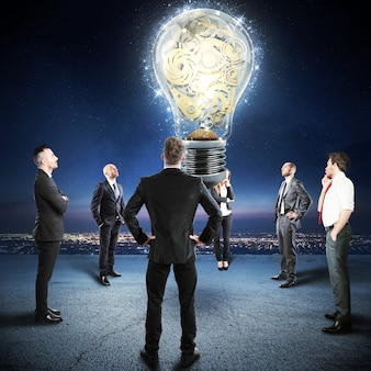 Squadra di uomini d'affari guarda una grande lampadina con meccanismo a ingranaggi