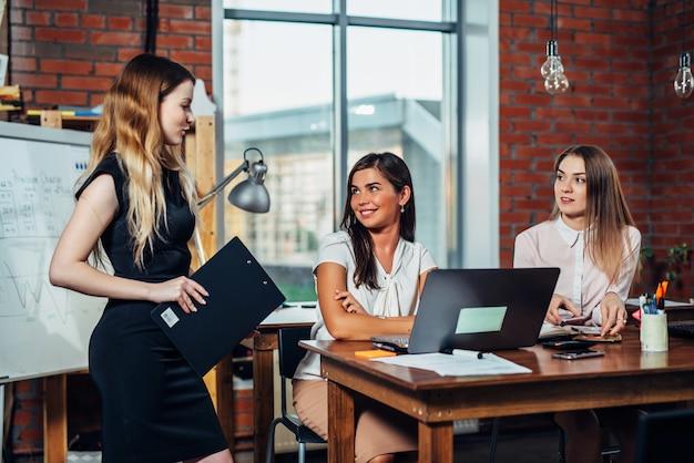 Team di donne d'affari che hanno una riunione per discutere di nuove idee che lavorano in un ufficio moderno.