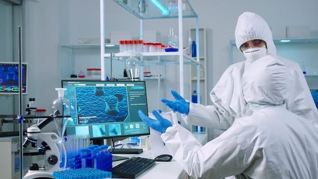 Team di chimici in tuta che lavora per sviluppare il vaccino in un laboratorio attrezzato. scienziati che esaminano l'evoluzione del virus utilizzando l'alta tecnologia per la ricerca scientifica sullo sviluppo del trattamento contro il covid19