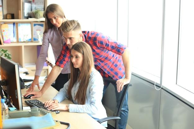 Team di colleghi che fanno brainstorming insieme mentre lavorano al computer