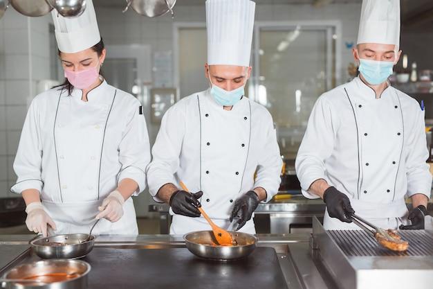 Squadra di cuochi che cucinano in un ristorante