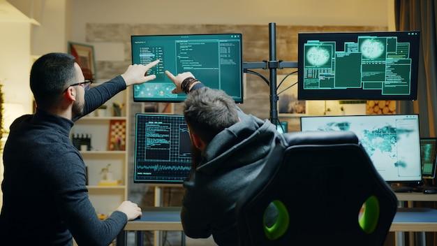 Team di pericolosi hacker maschi che utilizzano un potente computer per spiare il governo. violazione della sicurezza.