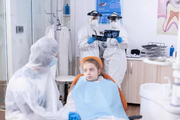 Team di dentisti che esaminano la radiografia dentale del paziente vestito in tuta nel corso dell'epidemia di coronavirus. stomatologo durante il covid19 che indossa una tuta in dpi facendo la procedura dei denti del bambino seduto