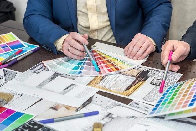 Team di designer che lavorano alla ristrutturazione dell'appartamento con proiettori moderni scegliendo il colore su campionatore arcobaleno, laptop e strumenti. interno di casa