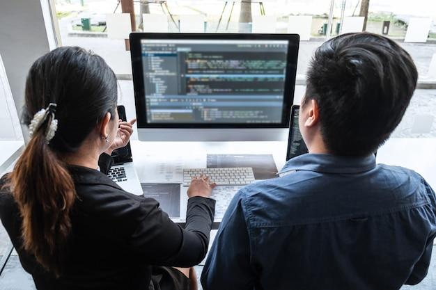 Team di programmatore sviluppatore che lavora al progetto nel computer di sviluppo software nell'ufficio dell'azienda it, scrittura di codici e sito web di codici dati e tecnologie di database di codifica per trovare la soluzione del problema.