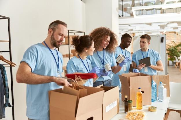 Team di diversi volontari in guanti protettivi che smistano gli alimenti per l'imballaggio in scatole di cartone