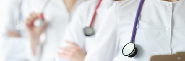 Il team di medici in camice bianco e stetoscopi sta insieme