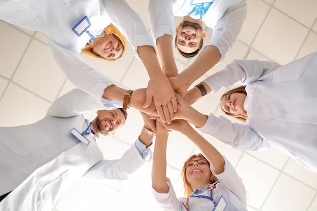 Team di medici che uniscono le mani, vista dal basso