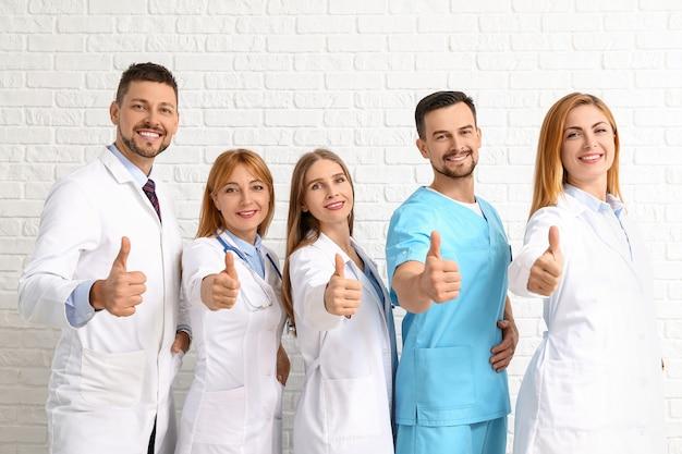 Team di medici che mostrano il gesto del pollice in su sulla superficie del mattone bianco