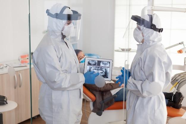 Team di medici che indossano un'uniforme di protezione antivirus completa in piedi vicino al paziente, analizzando i raggi x digitali dei denti utilizzando il trattamento di pianificazione del tablet