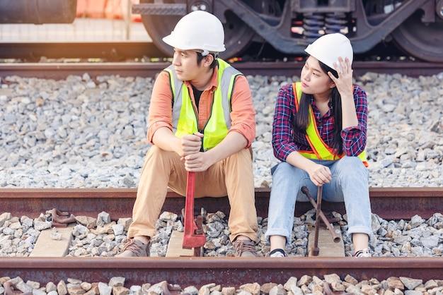 Ingegnere del team che tiene la chiave per la riparazione che lavora sul sito del treno, sicurezza, civile, lavoratori