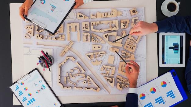 Team di ingegneri e architetti che lavorano, pianificano, misurano il layout del progetto edilizio nella riunione della sala del consiglio, vista dall'alto