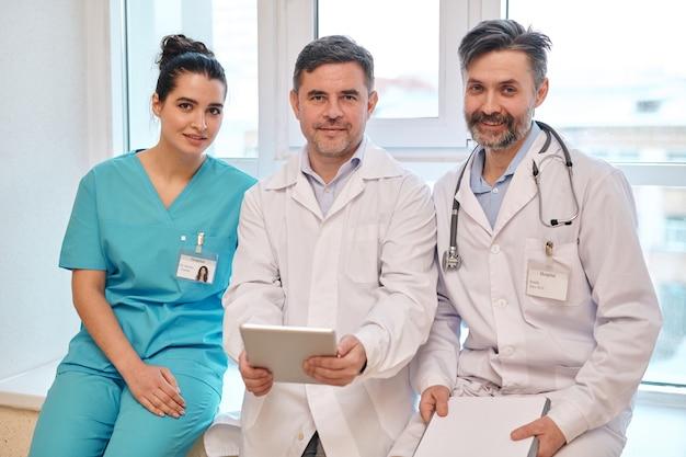 Team di personale medico esperto in uniforme che si siede sul davanzale della finestra in ospedale e che guarda l'obbiettivo