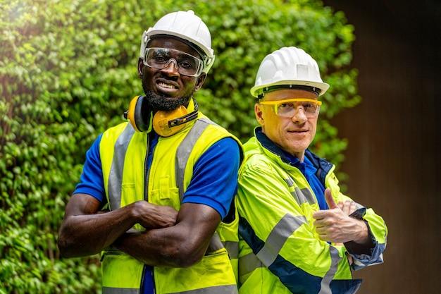 Uomini dell'ingegnere tecnico dell'operaio di fabbrica della squadra che stanno fiducia con il vestito verde della suite di lavoro
