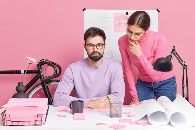 Il team di architetti femminili e maschili lavora sul progetto collabora alla posa di un nuovo progetto di costruzione sul desktop con carte circondate da adesivi
