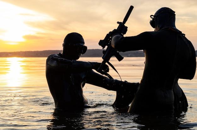Squadra di combattenti di un'unità speciale si muovono sull'acqua per completare l'attività. il concetto di instabilità, operazioni militari, guerra fredda. tecnica mista