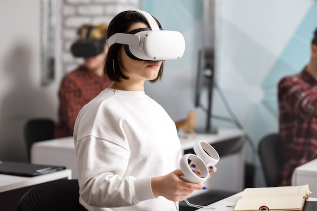 Team di quattro ingegneri creativi che lavorano con la realtà virtuale, giovane donna che prova occhiali o occhiali vr seduti nella stanza dell'ufficio