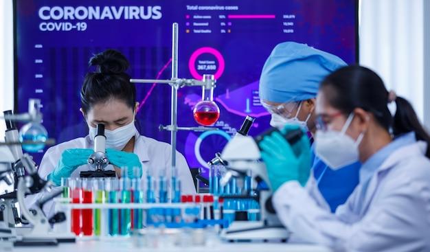 Le ricercatrici del gruppo di squadra si sono concentrate sul lavoro con il microscopio e le apparecchiature di laboratorio nella stanza del laboratorio tra provette e bicchieri. concetto per il duro dovere degli scienziati nell'epidemia di covid-19.