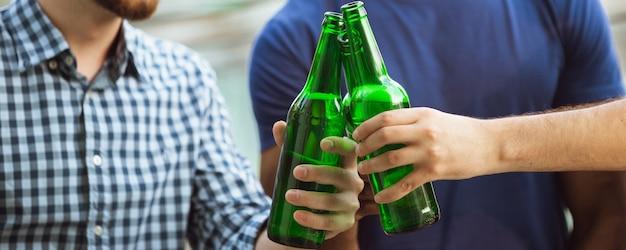 Squadra. mani di amici, colleghi mentre bevono birra, si divertono, tintinnano bottiglie, bicchieri insieme.