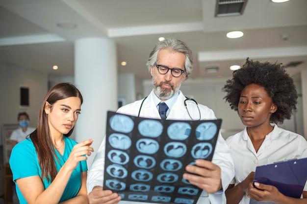 Team di operatori sanitari alla ricerca di radiografie dei polmoni del paziente. medico maschio e femmina che esamina i raggi x dei polmoni in ospedale durante la pandemia di covid19