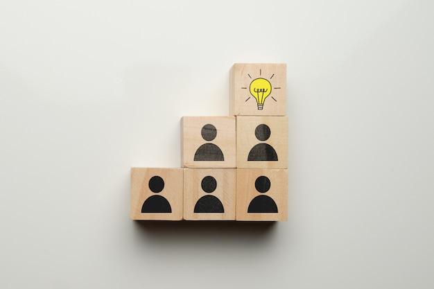 Concetto della generazione di idea e del gruppo con le icone sui blocchi di legno.