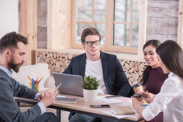 Guida del gruppo. uomo intelligente bello serio seduto al tavolo e guardando la sua squadra mentre lavora con loro