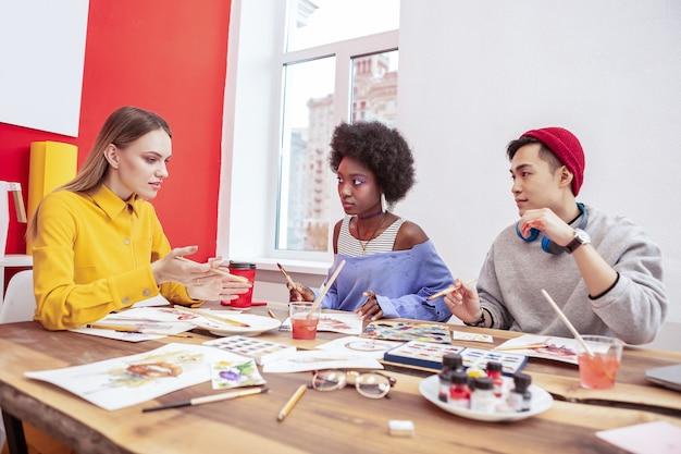 Guida del gruppo. due talentuosi apprendisti creativi della rivista di moda che ascoltano il loro team leader