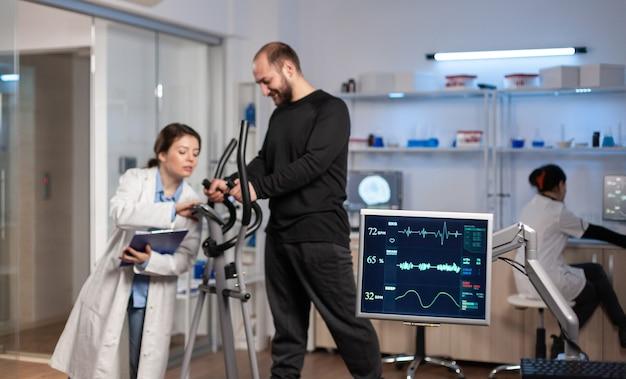 Team di ricercatori mediali che monitorano il vo2 degli sport da prestazione dell'uomo che indossano la maschera in esecuzione. medico di laboratorio che misura la resistenza dello sportivo mentre la scansione ekg viene eseguita sullo schermo del computer in laboratorio.