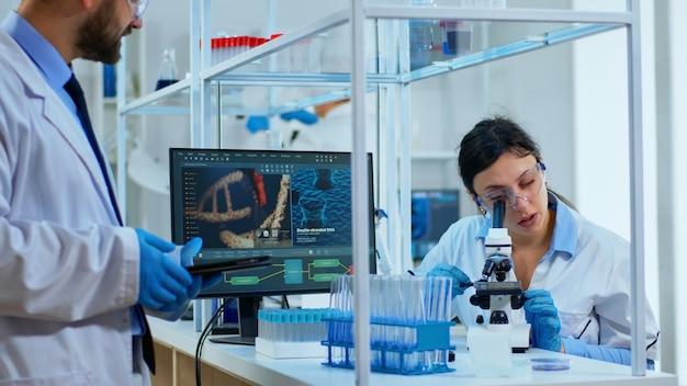 Scienziato medico del team che conduce esperimenti sul dna al microscopio digitale scrivendo i risultati su tablet lavorando nel laboratorio di scienze. ingegnere di laboratorio caucasico in camice bianco che analizza lo sviluppo del vaccino