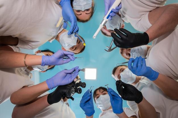 Team di operatori sanitari che tengono gli strumenti dentali sulle mani e fanno un cerchio. concetto di unità