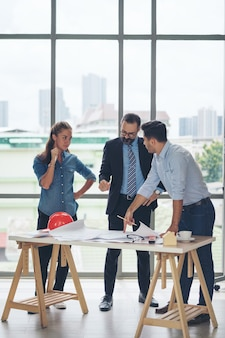 Team di architetti multietnici che lavorano su piani di costruzione in sala riunioni. ingegneri che discutono sul progetto in ufficio. uomo d'affari maturo e donna in piedi intorno al tavolo che lavora al progetto.