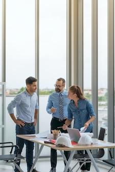 Team di architetti multietnici che lavorano su piani di costruzione in sala riunioni. ingegneri che discutono sul progetto in ufficio.