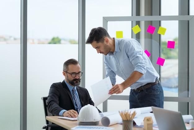 Team di architetti multietnici che lavorano su piani di costruzione in sala riunioni